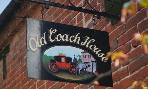 Old Coach House Hanging Business Signs in Miami, FL
